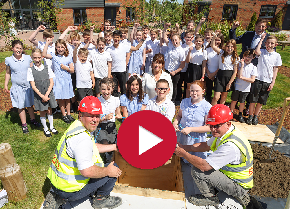 Children from Davington Primary School bury a time capsule with Anderson employees at Faversham Lakes